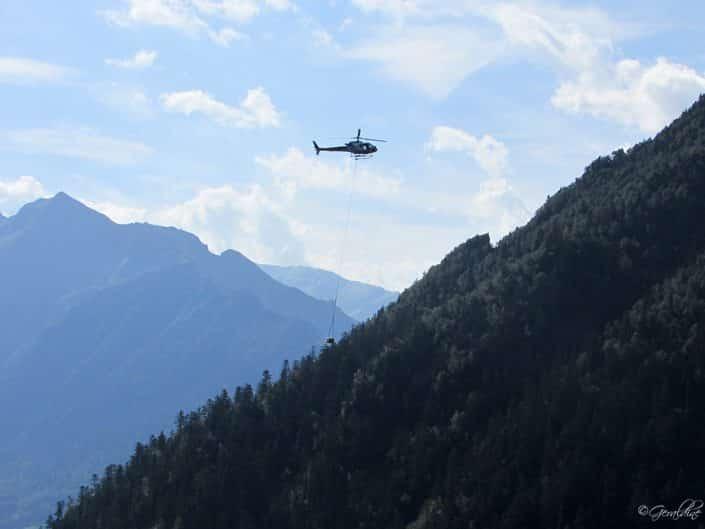 Un hélicoptère portant du matériel de rénovation d'un conduit d'eau